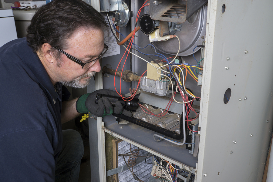 HVAC technician doing furnace services
